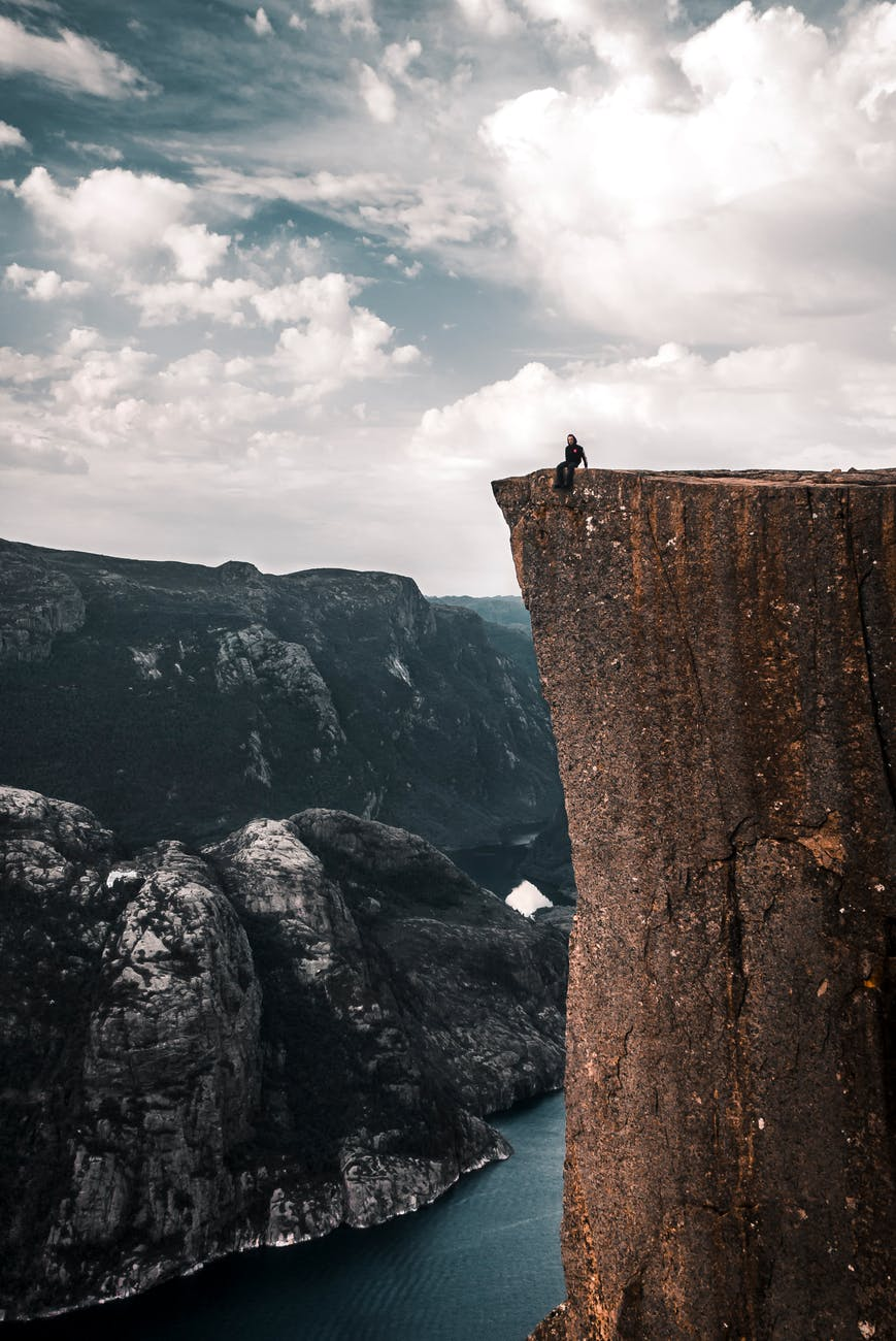 people sitting on the edge of a cliff