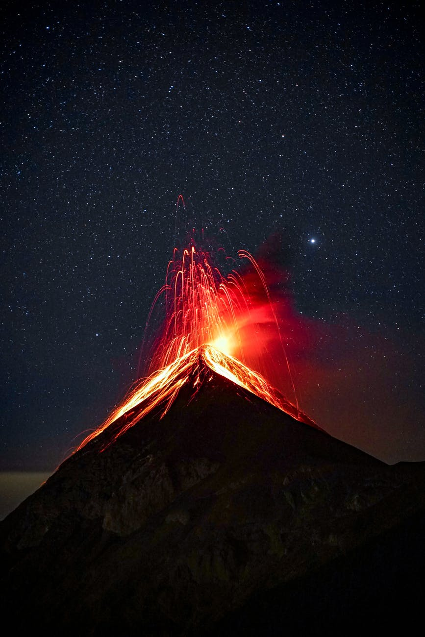 volcano erupting at night under starry sky